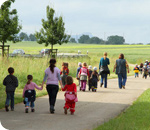 kids and teachers walking on a country road